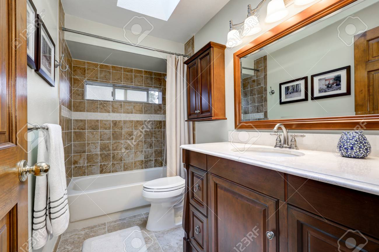Traditional Bathroom With Skylight Over Dark Brown Vanity Paired