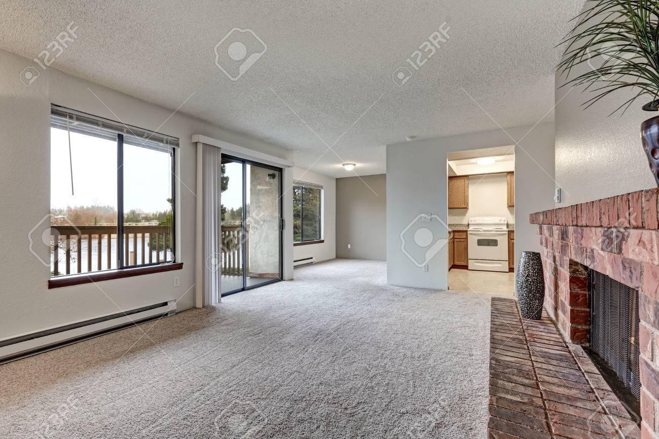 Salon vide avec murs blancs, moquette au sol, cheminée en brique rouge et  sortie sur le balcon. Nord-ouest, États-Unis
