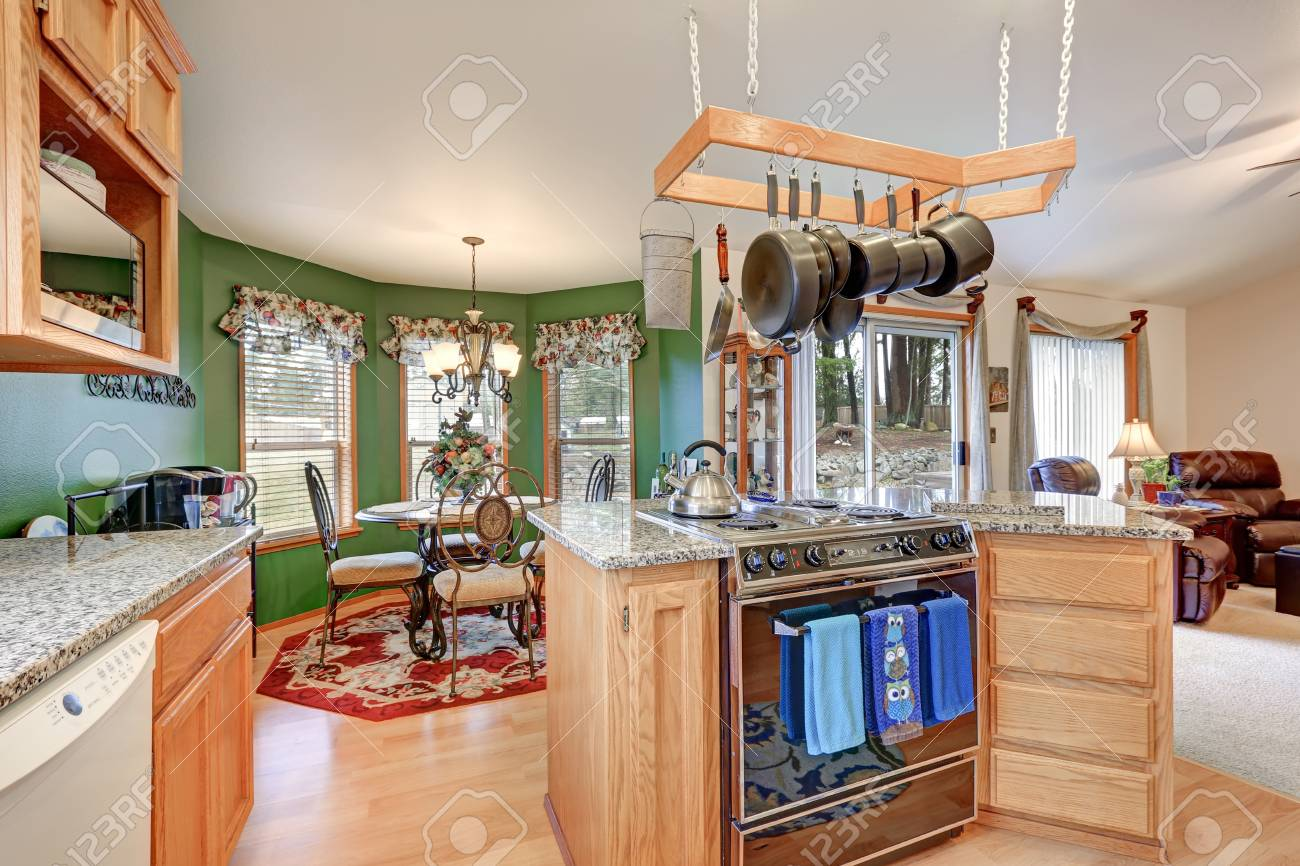 Bright rambler kitchen boasts vaulted ceiling over bar style kitchen island with kitchen hanging rack above