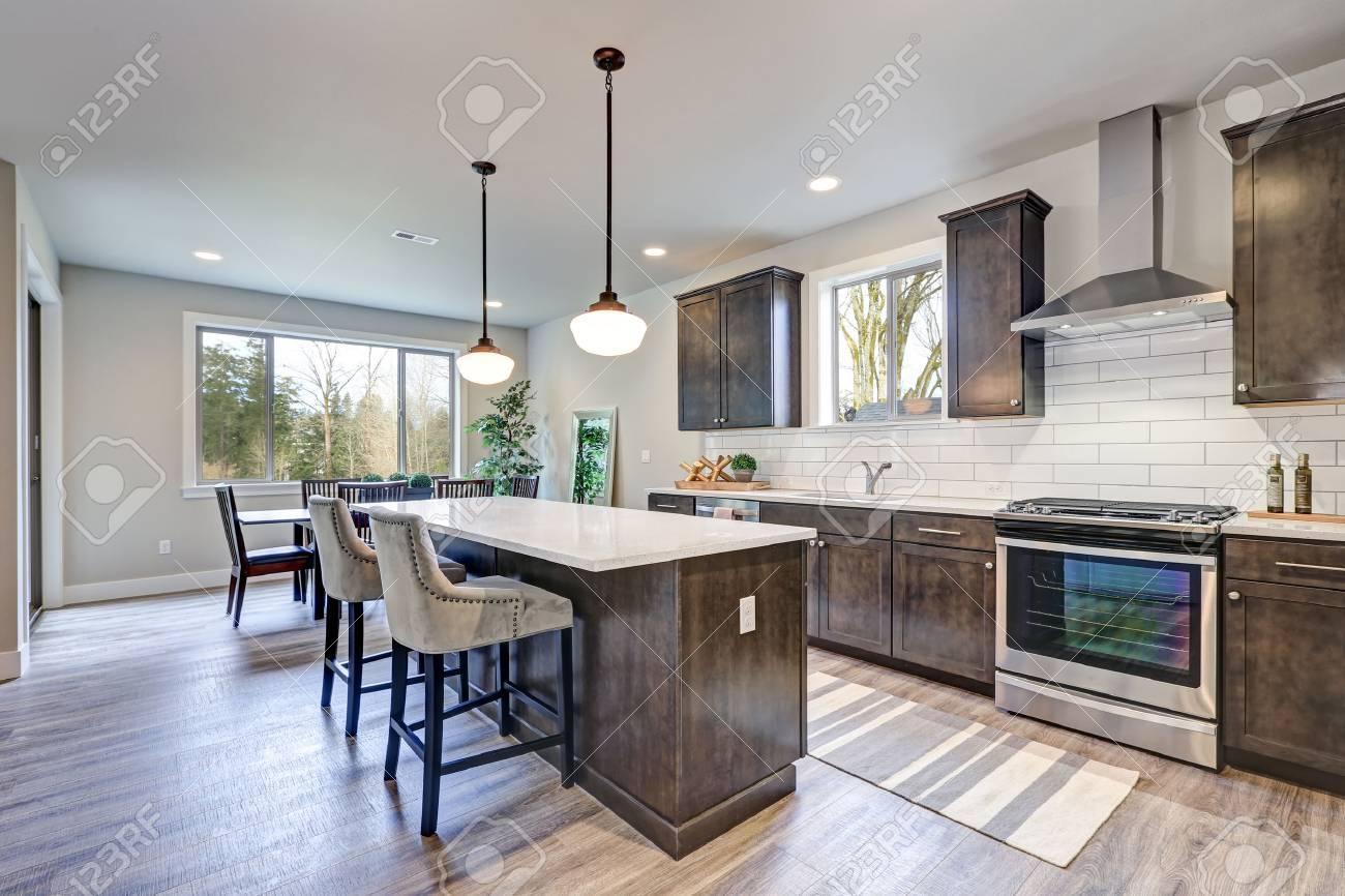 - New Kitchen Boasts Dark Wood Cabinets, White Backsplash Subway