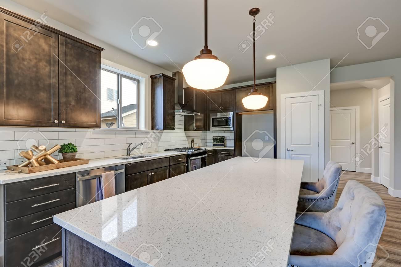 La nuova cucina vanta armadi in legno scuro piastrelle in metallo