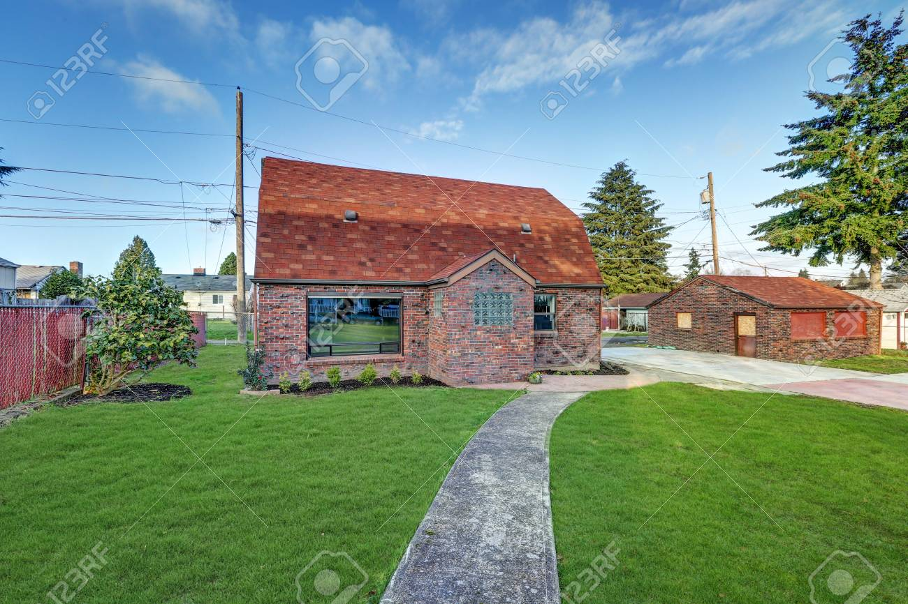 Small red brick home exterior with detached