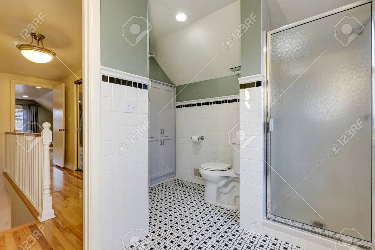 bathroom features subway tiled half walls with black tile border