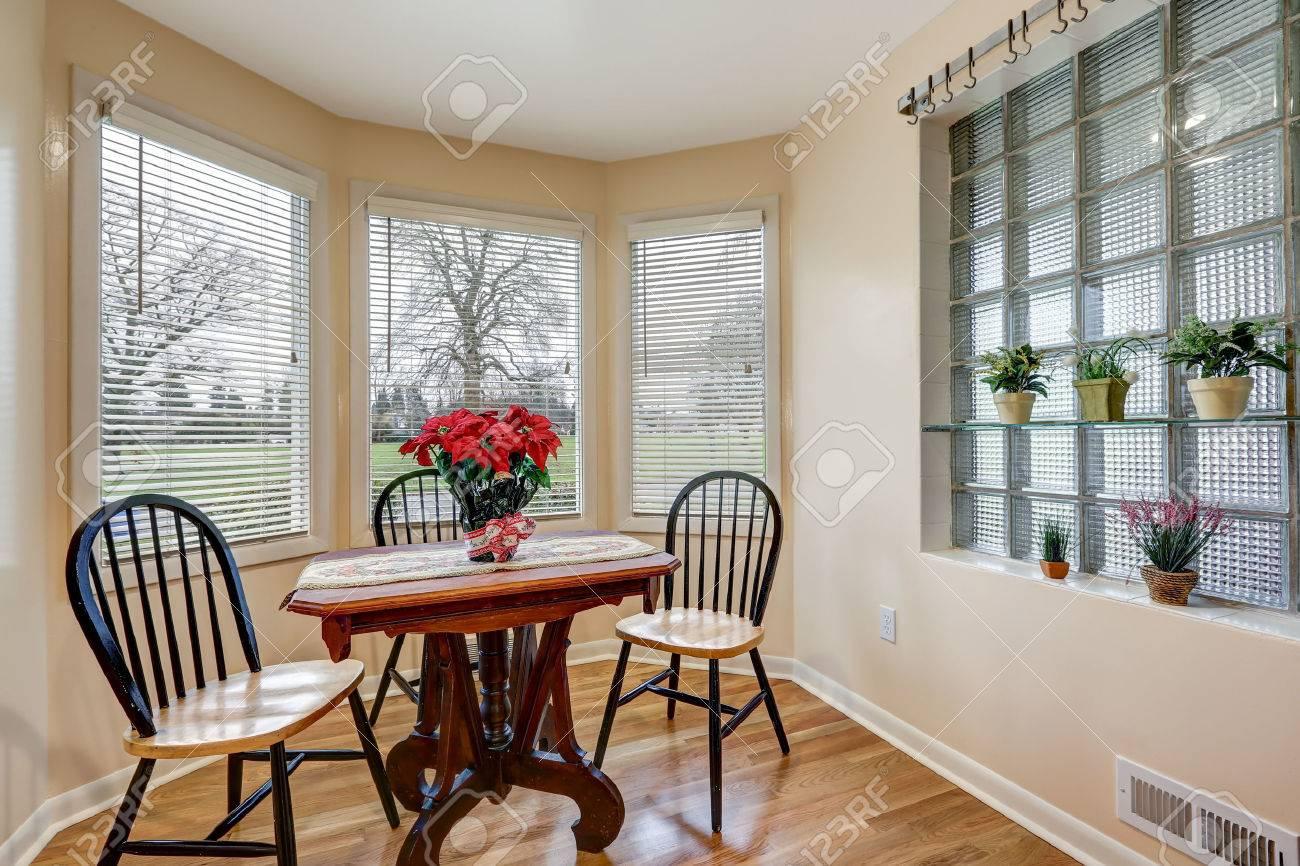 Rangement petit-déjeuner rempli de lumière avec des murs de pêche durables  meublés avec une table de piédestal vintage et des chaises arrière rondes  ...