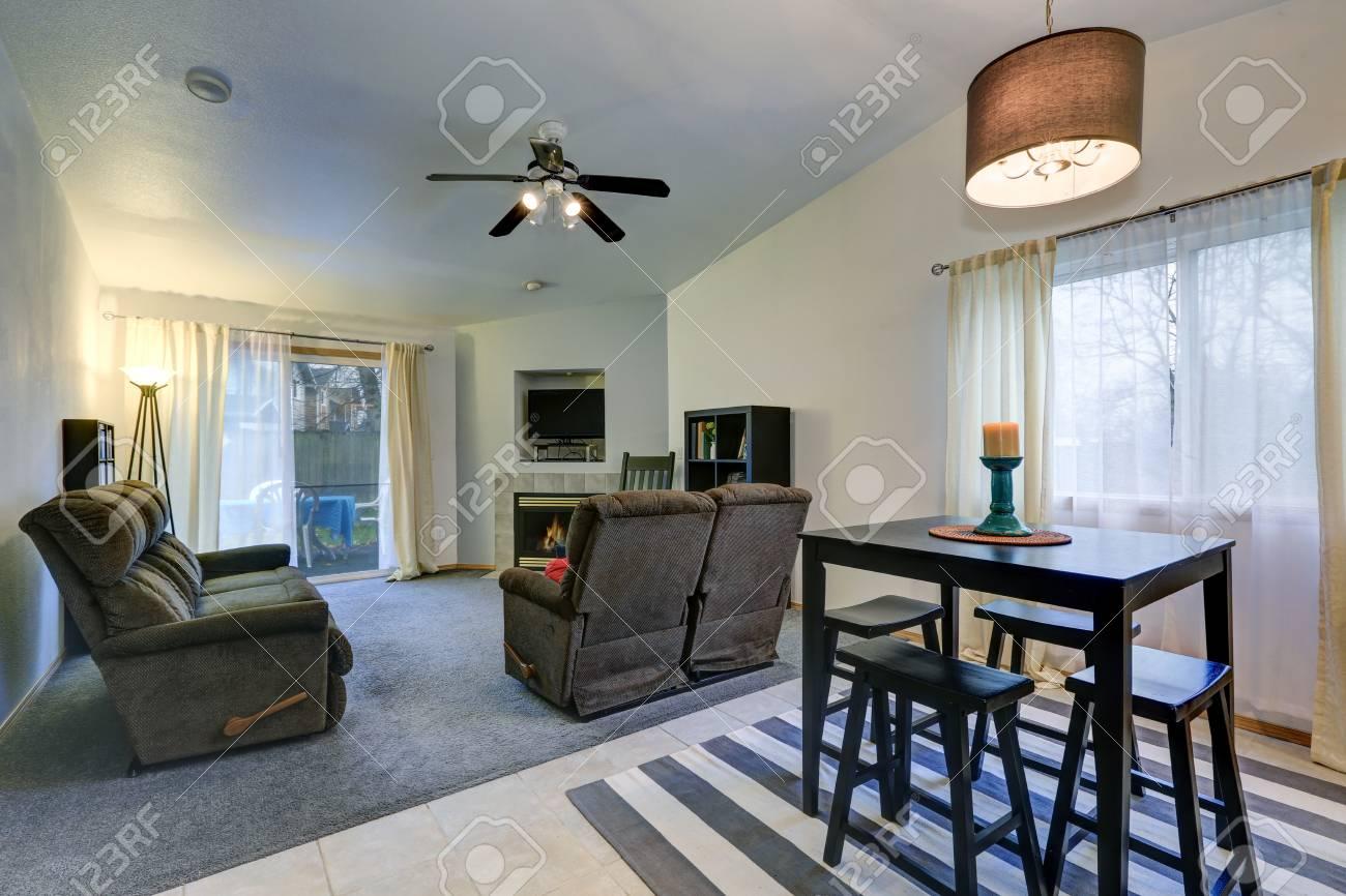 Salle A Manger Gris Blanc Noir l'intérieur de la salle à manger et du salon avec plafond voûté dispose  d'une table à manger noire avec des bancs sur un tapis rayé gris et blanc  et