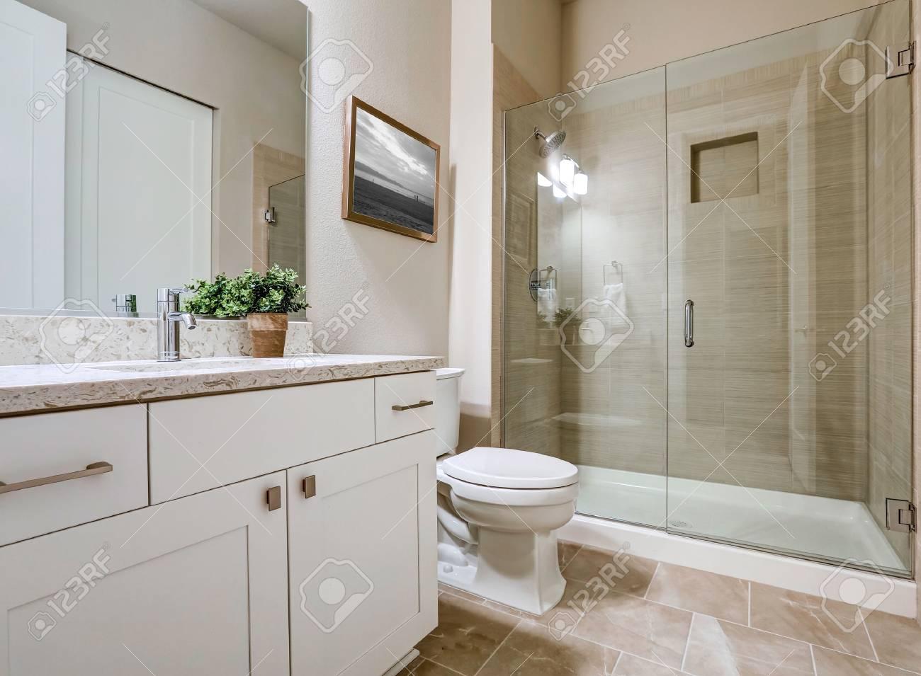Transitional design d\'intérieur de salle de bains dans des couleurs douces  beige. Caractéristiques douche en verre avec encadrement carreaux taupe ...