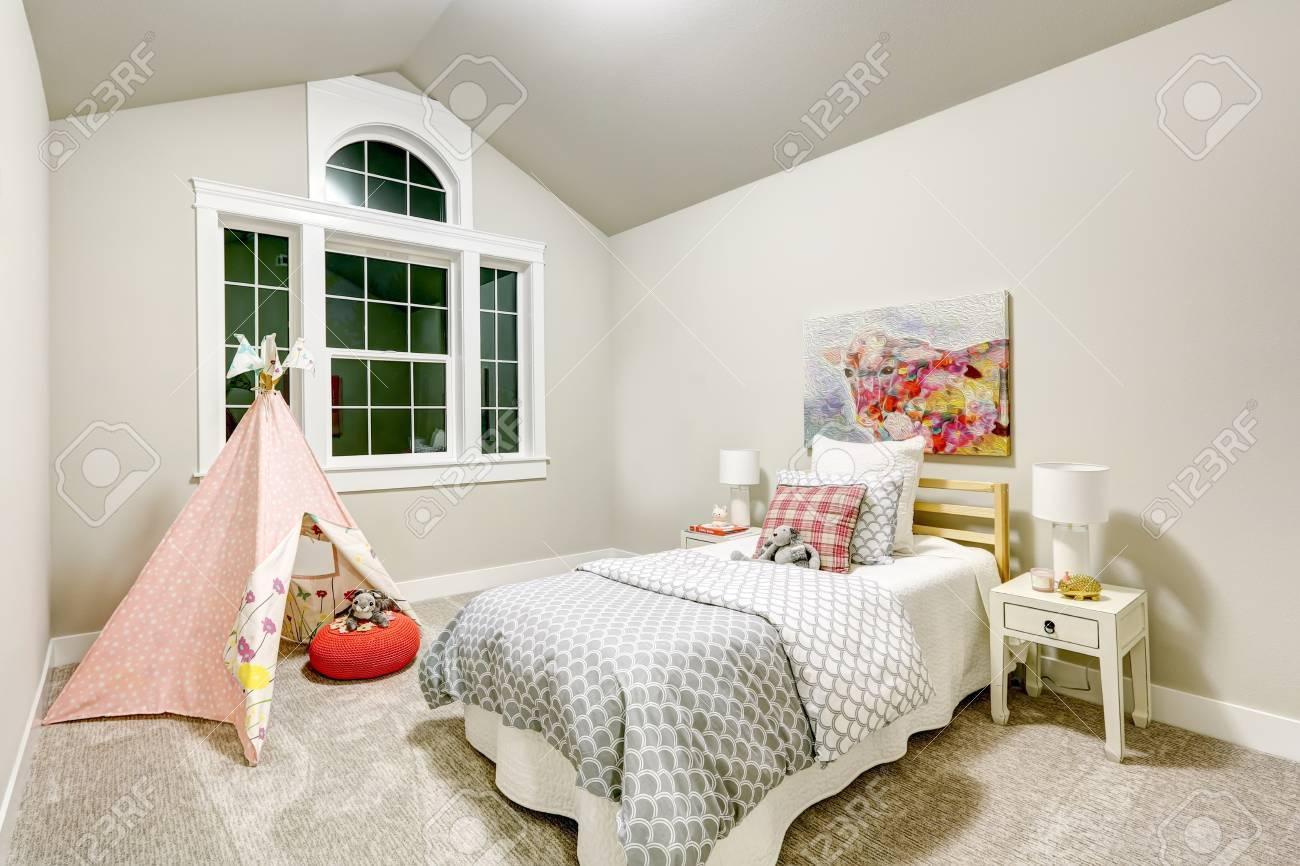 La chambre de la fille gris clair dispose d\'un plafond voûté sur un lit  blanc et gris recouvert d\'oreillers et de jouets et d\'une tente de teepee  rose ...