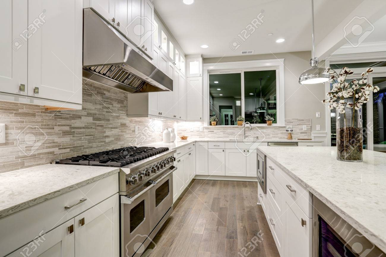 Gourmet kitchen features white shaker cabinets with marble countertops, stone subway tile backsplash and gorgeous kitchen island. Northwest, USA - 72942201