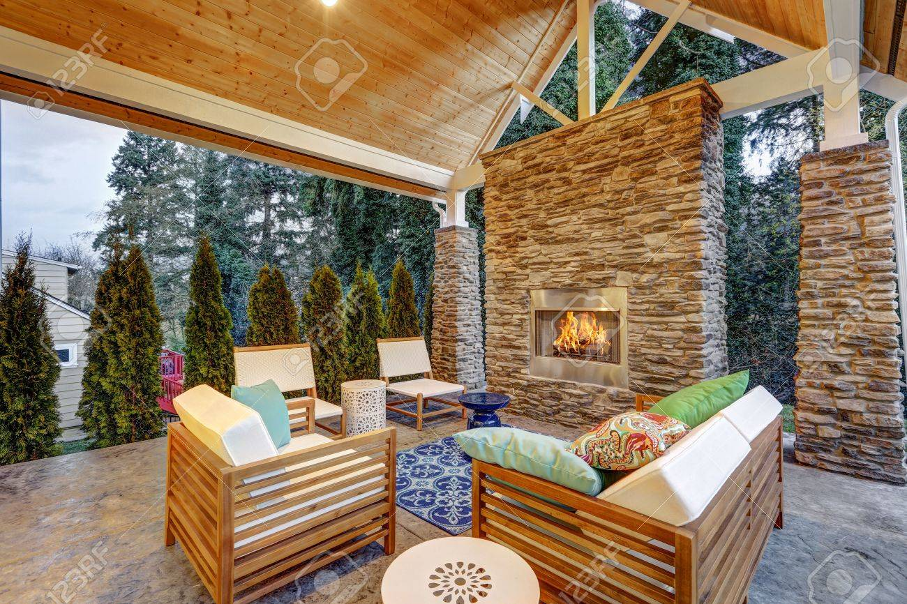 Chic covered back patio with built in gas fireplace, stone pillars, plank vaulted ceiling over cozy teak wood sofa set topped with white cushions and green pillows. Northwest, USA - 72961423