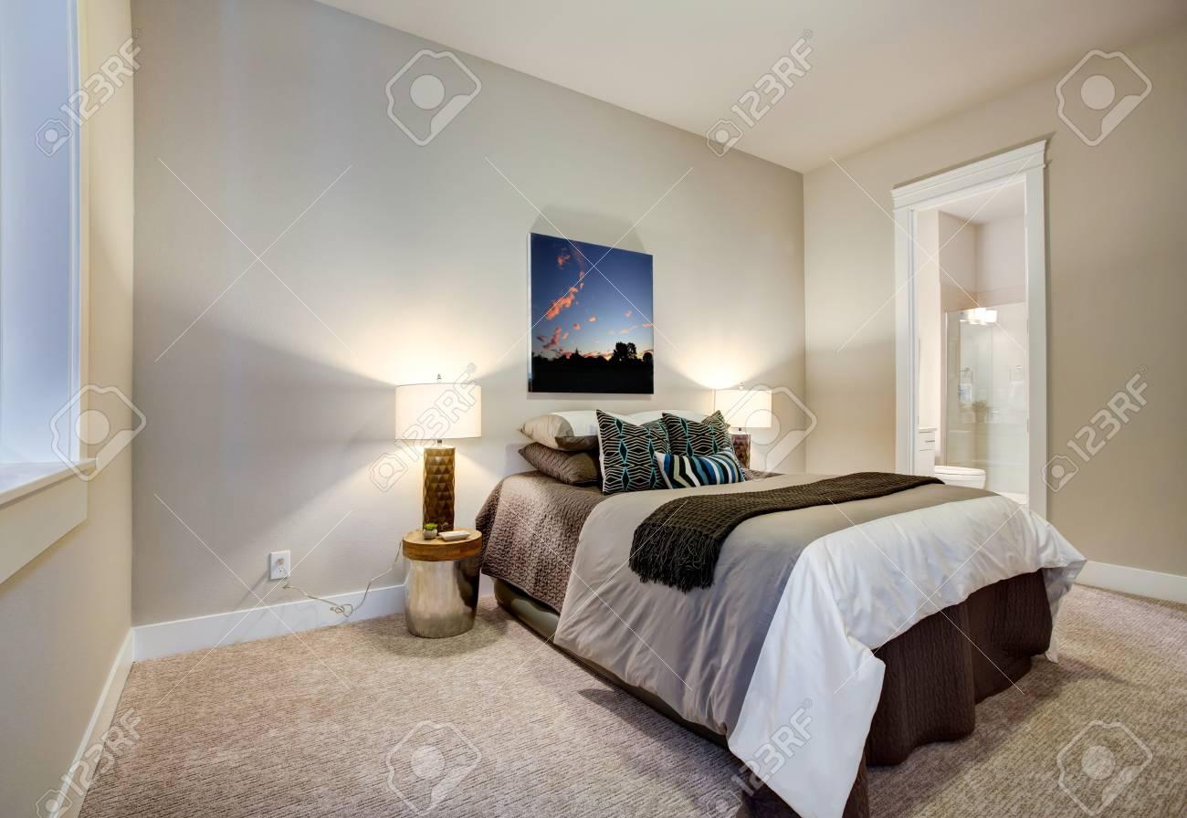 La chambre neutre est dotée d\'une salle de bains privative avec des murs  peints en beige et une literie marron chocolat assortie à des oreillers à  ...