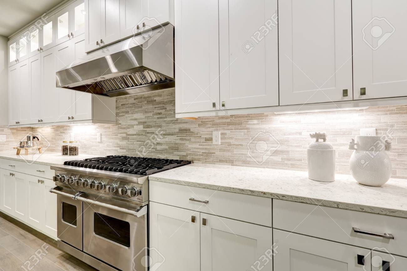 Gourmet kitchen features white shaker cabinets with marble countertops paired with stone subway tile backsplash and stainless steel hood over eight burner gas range. Northwest, USA - 89679773