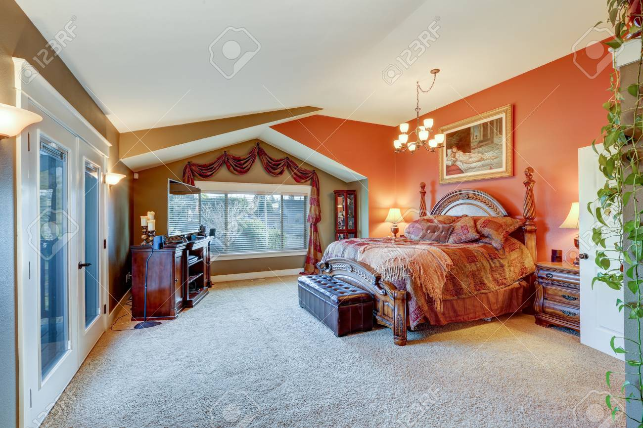Tele Au Pied Du Lit légante suite master avec plafond voûté, murs rouges et taupe, magnifique  lit queen sculpté en bois avec banc en cuir tufté à l'armoire multimédia