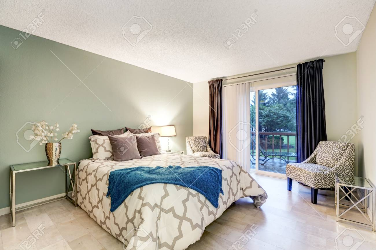 Master bedroom showcases pale green accent wall, queen size bed..