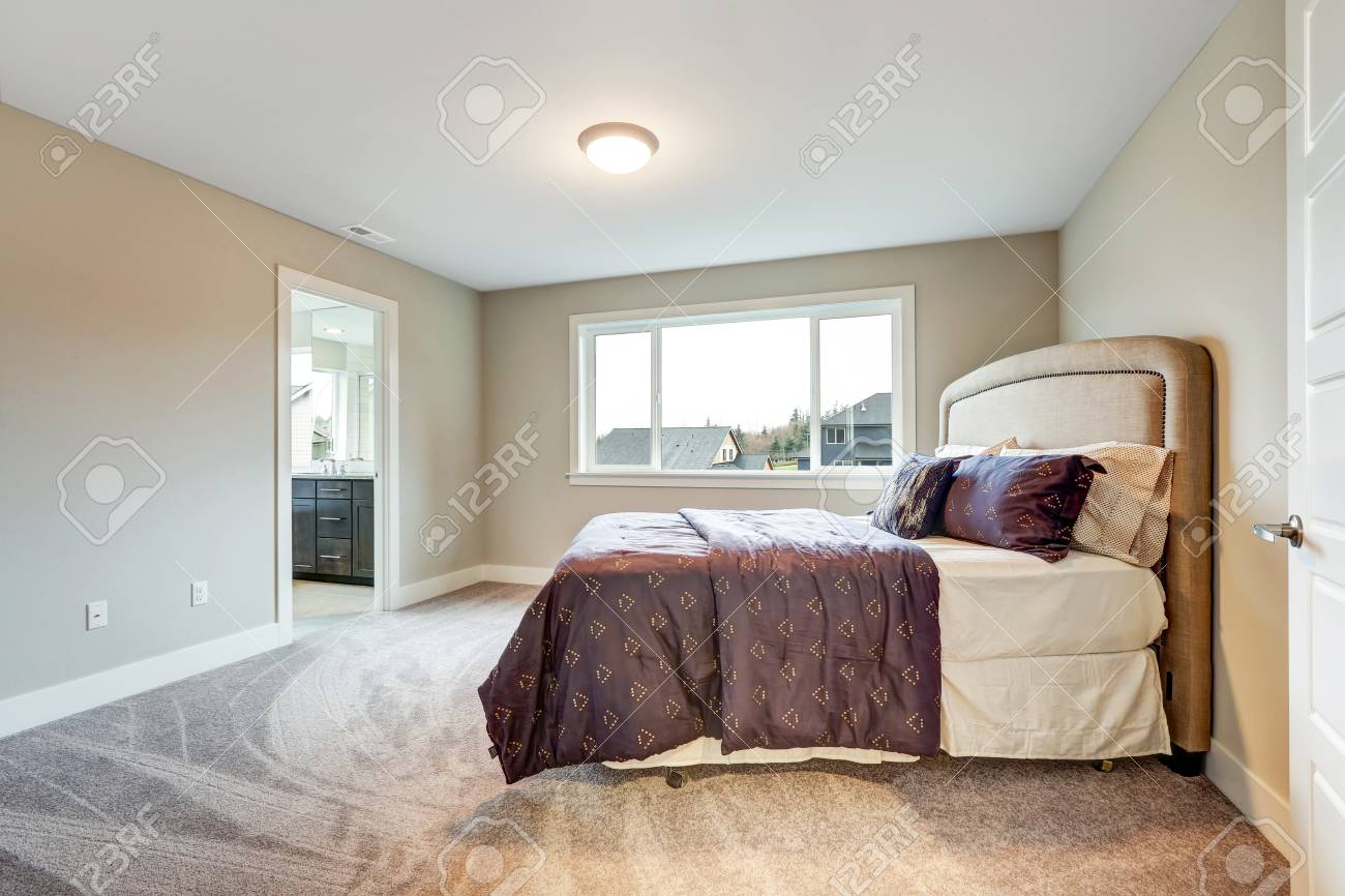 Beige master bedroom with king size bed accented with upholstered..