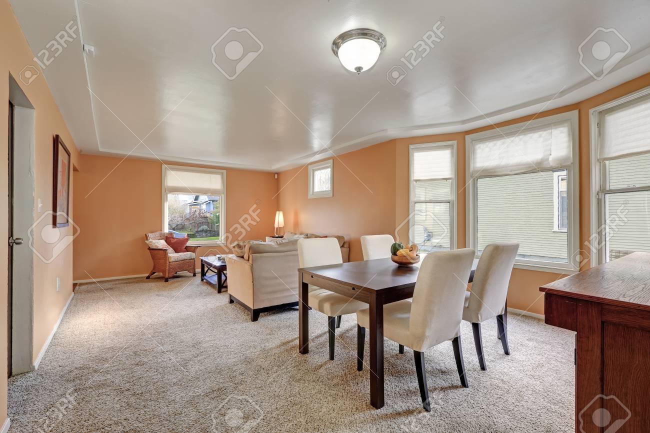 Acogedor salón y comedor interior con paredes de durazno, área de comedor  con una mesa de comedor teñida de oscuro y forrada con sillas tapizadas de  ...