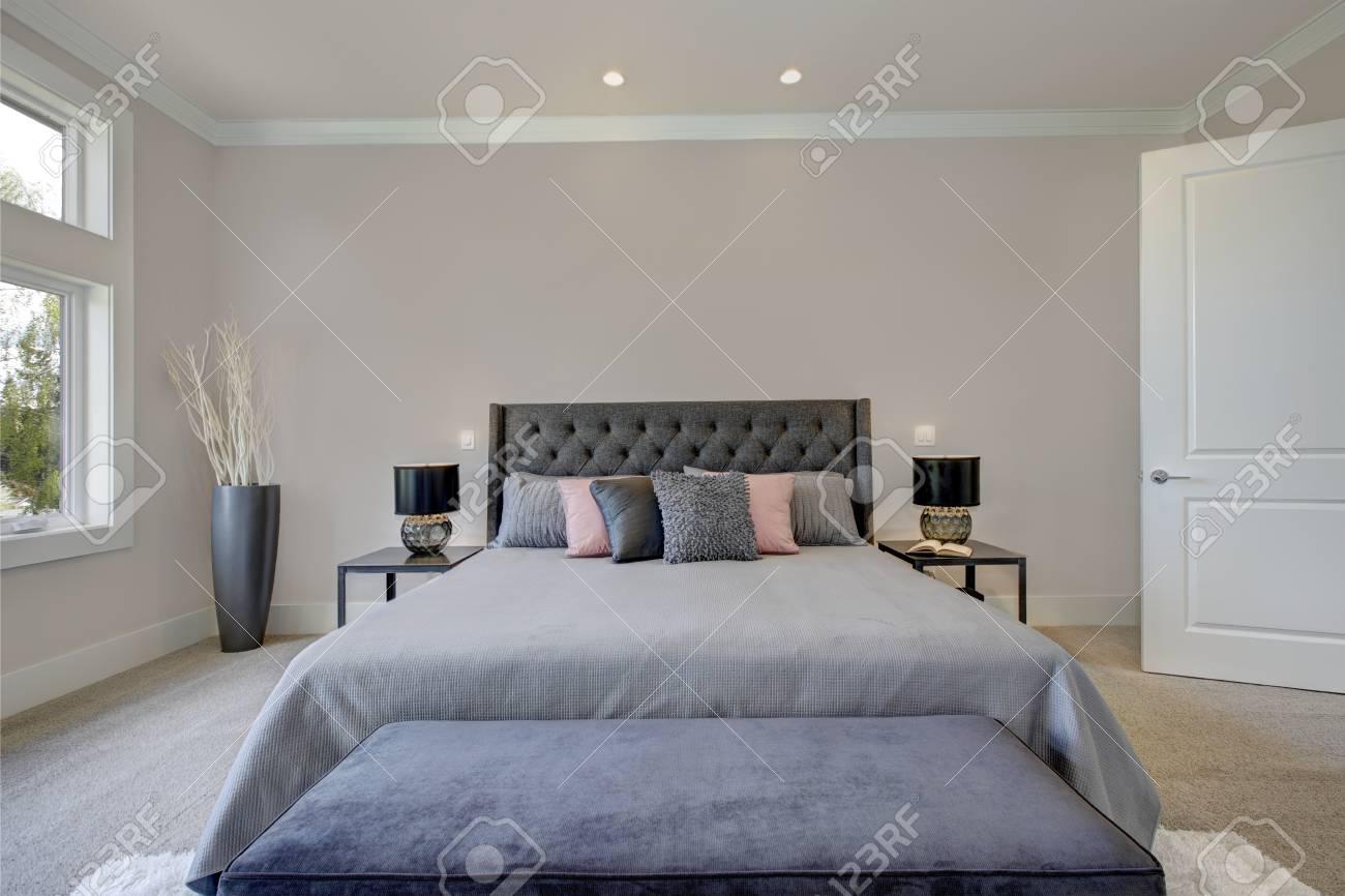 Camera da letto piena di luce mostra un letto king size con testata  capitonné vestito con lenzuola grigie e una panca di velluto blu scuro  posto su un ...
