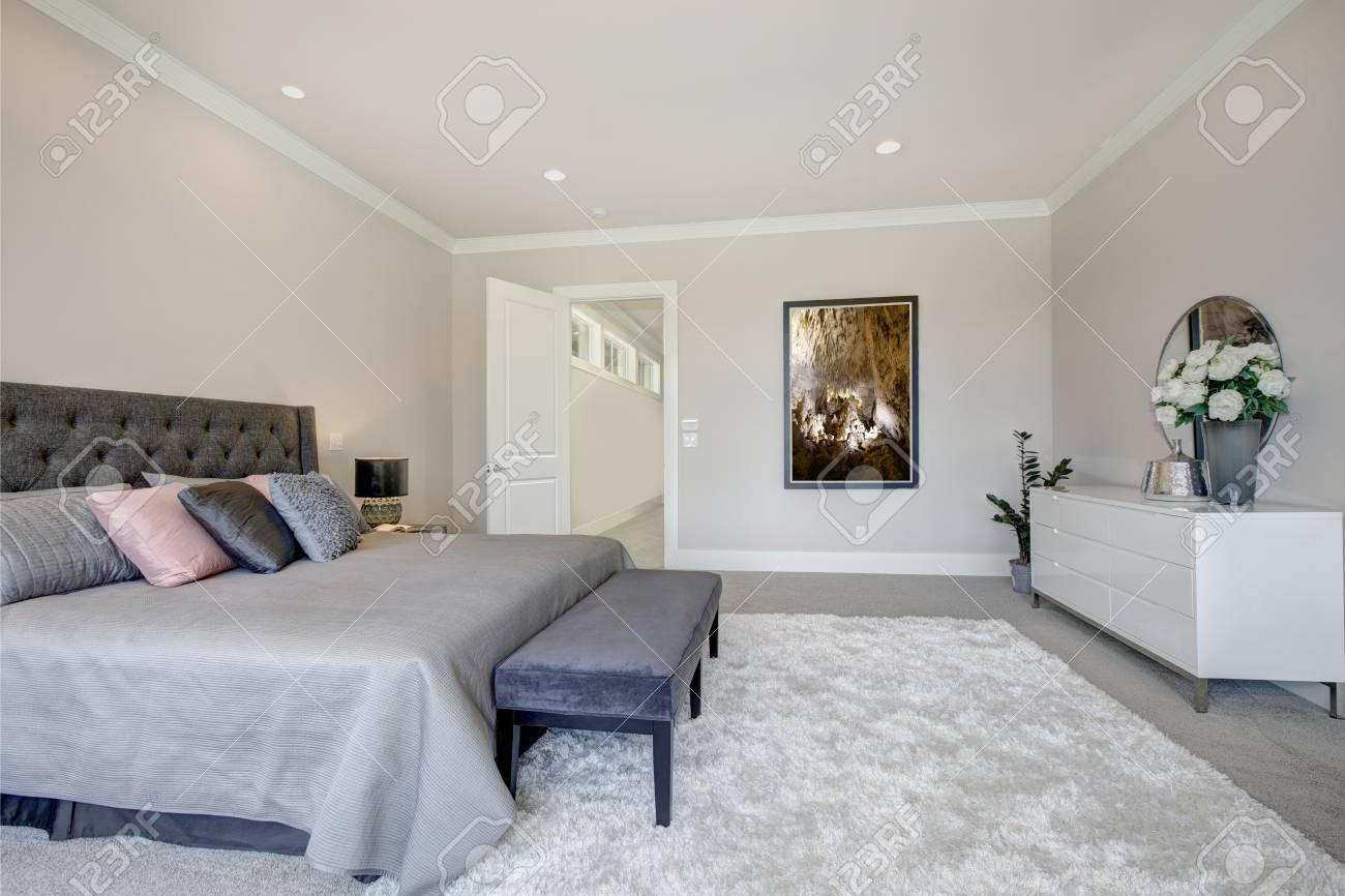 La luminosa camera da letto presenta un letto king size con testata  capitonné, vestita con lenzuola grigie e una panca di velluto blu scuro  posta su ...