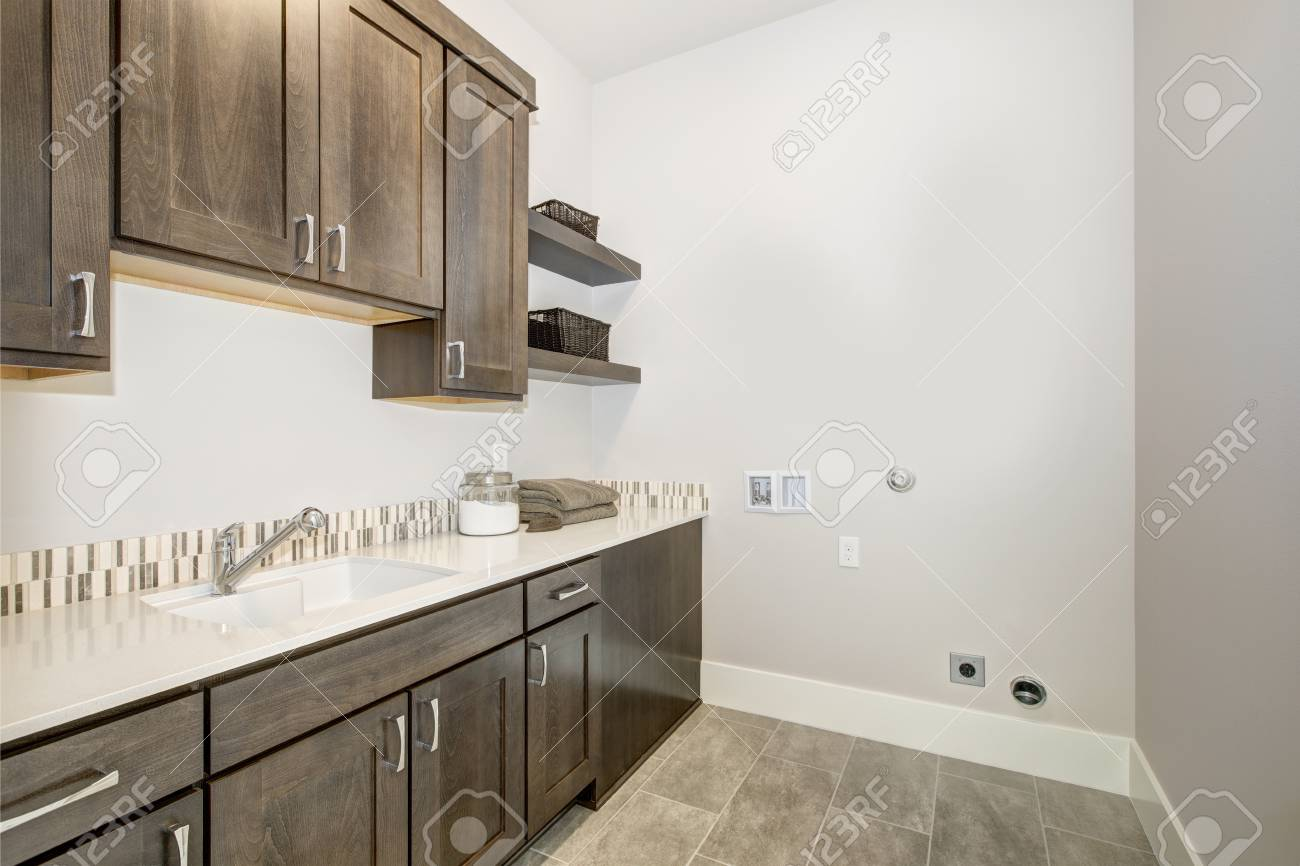 Beautiful Laundry Room With Dark Brown Cabinets Paired With White