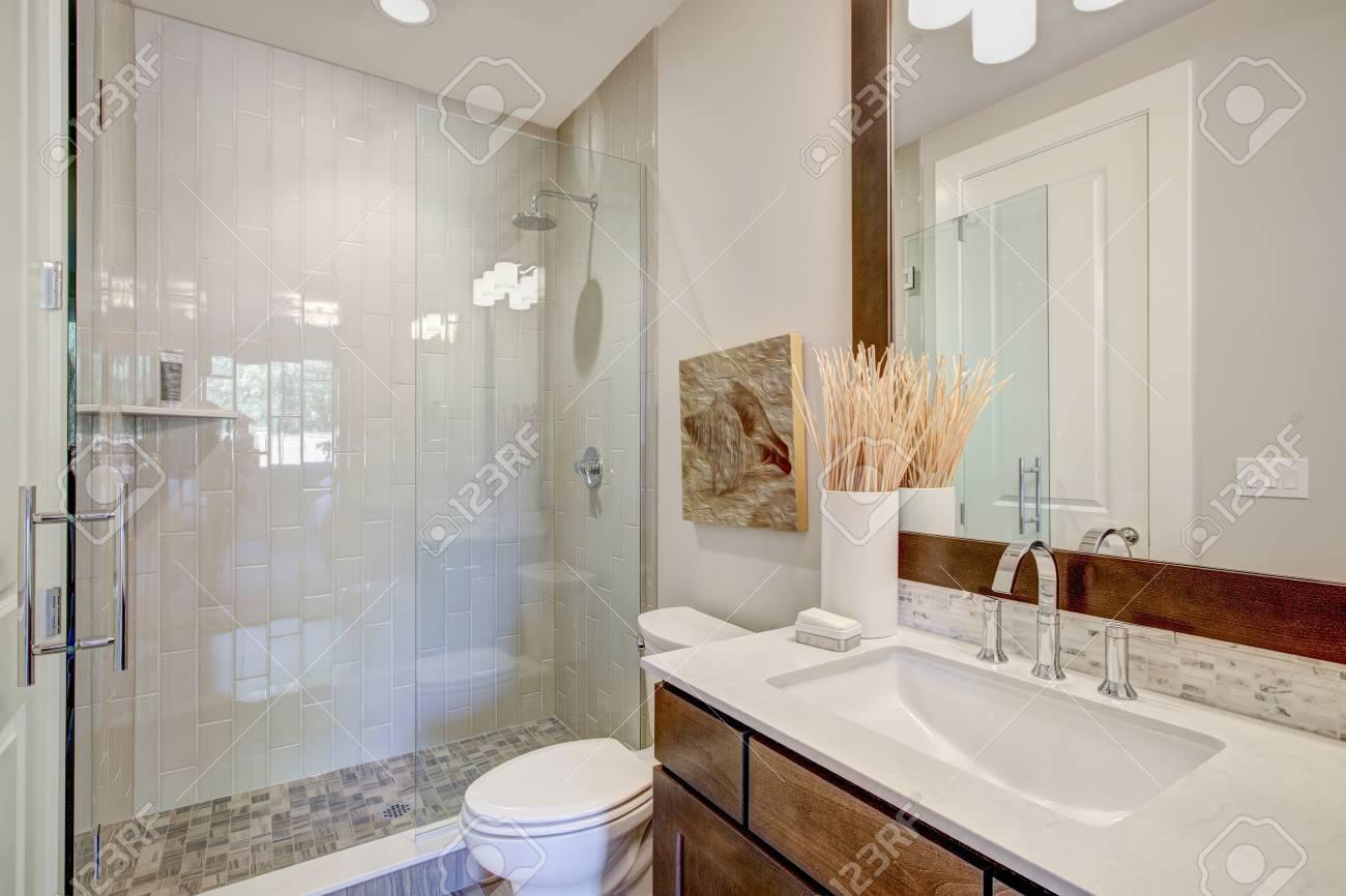 Salle de bain moderne dispose d\'une vanité de salle de bain équipée d\'un  lavabo rectangulaire sous un grand miroir encadré et une douche de ...