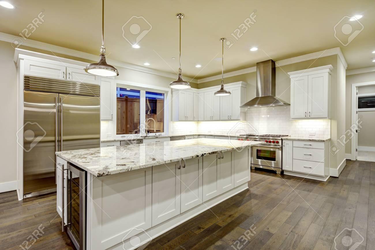 Diseño de cocina grande y espacioso con gabinetes de cocina blancos, isla  de cocina blanca con mucho espacio de almacenamiento, encimeras de granito  ...