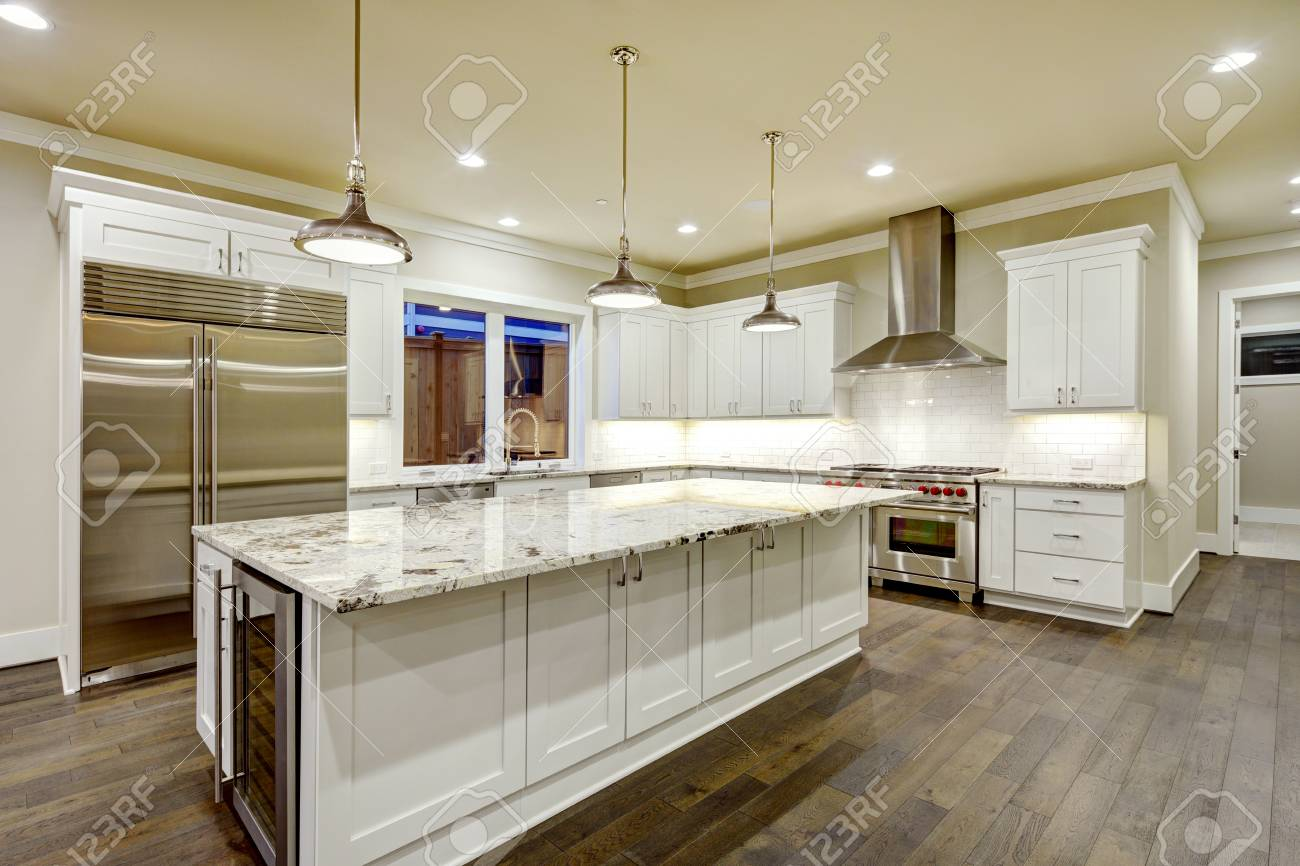 Large, spacious kitchen design with white kitchen cabinets, white..
