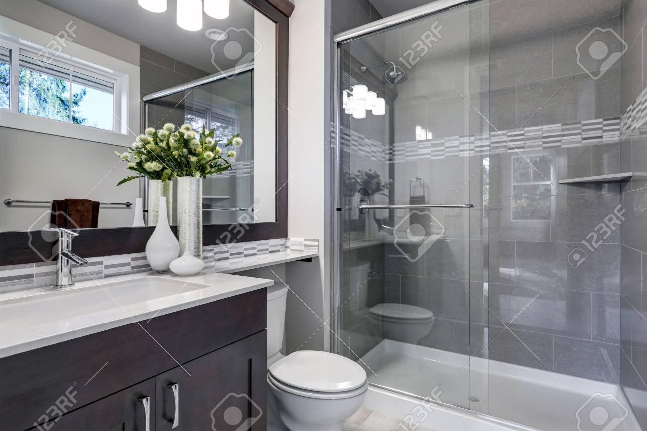 Nouvel intérieur de salle de bains lumineux avec douche à l\'italienne en  verre avec bordure en carrelage gris, meuble vasque brun surmonté d\'un ...