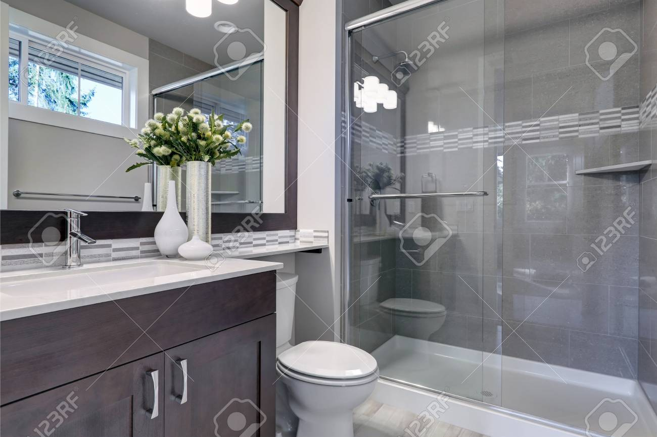Bright New Bathroom Interior With Glass Walk In Shower With Grey