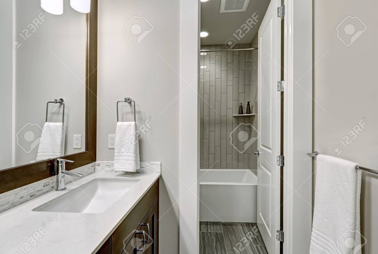 White And Brown Bathroom Boasts A Nook Filled With Double Vanity ...