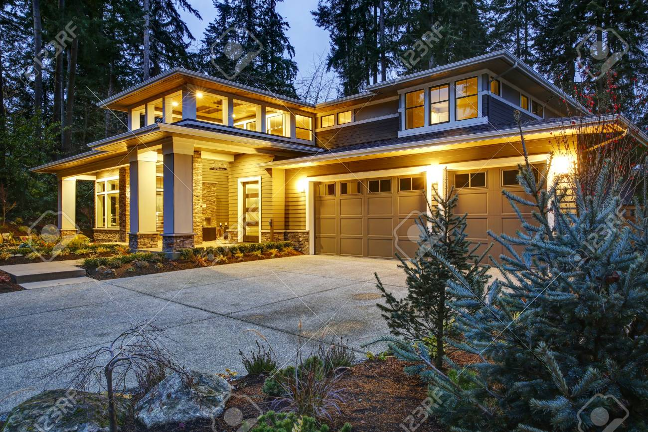 Luxurious new construction home exterior at sunset. View of two garage spaces with concrete driveway and illuminated porch with columns. Northwest, USA - 93635527