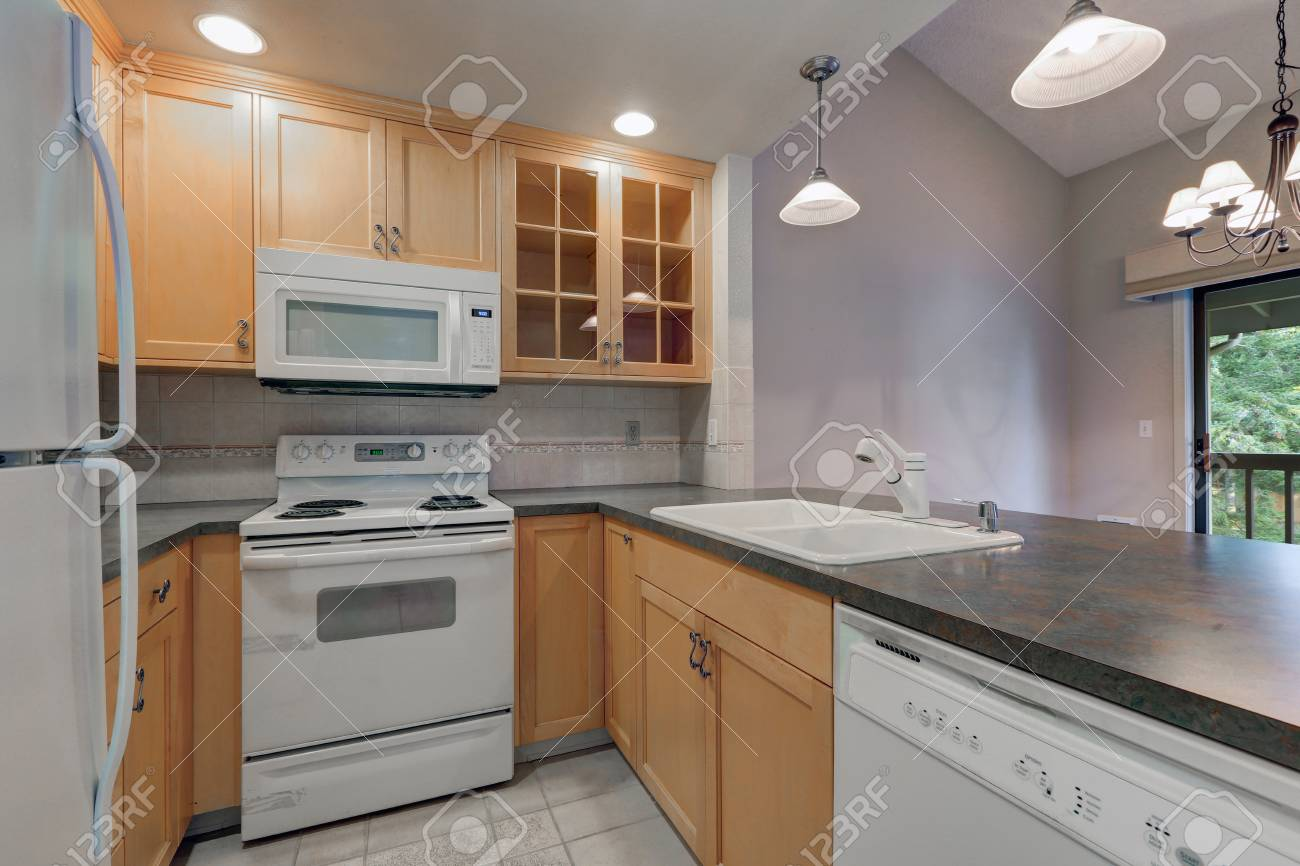 Tidy Compact Kitchen With Maple Cabinets Dark Grey Counters Stock Photo Picture And Royalty Free Image Image 93688556