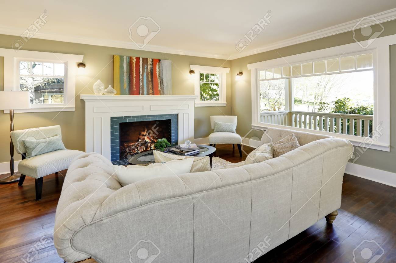 Lovely green living room with crown molding and a wood burning..