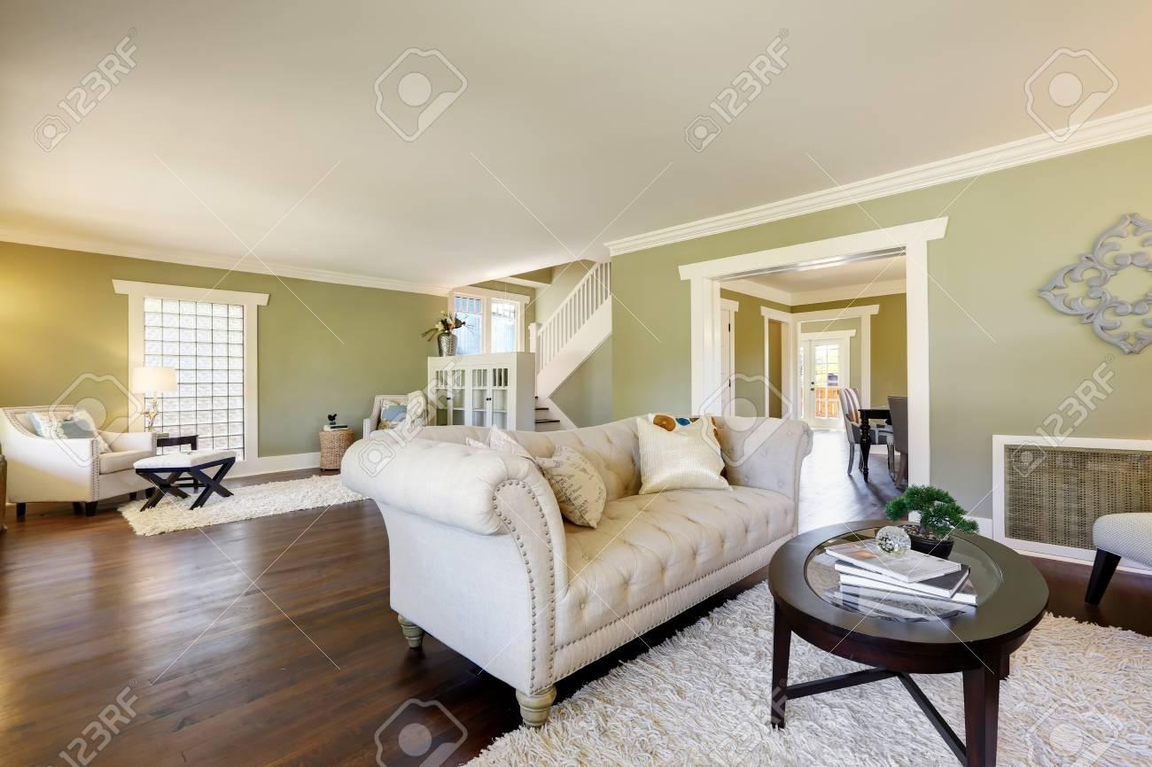 Lovely green living room with built-in bookshelves, crown molding