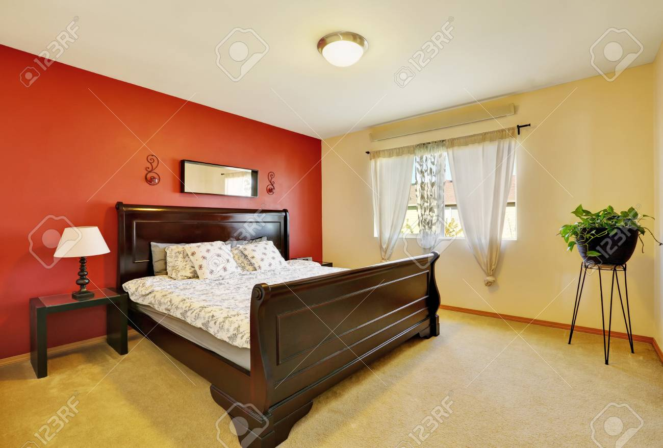 Chic master suite with red accent wall, a king size bed and elegant..