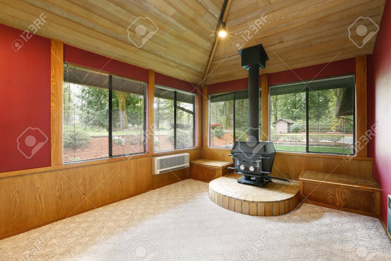 Bright empty living room interior with red accent walls, vaulted..