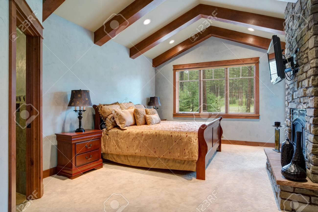 Chic master bedroom: vaulted ceiling with wooden beams over the..