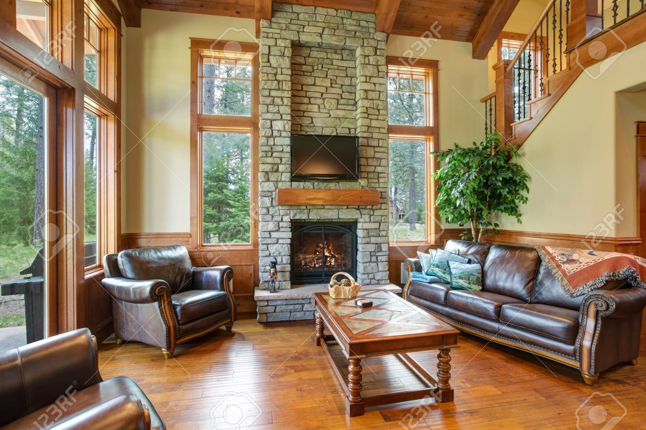 Gentil Stock Photo   Stunning Living Room Design Includes A Stone Wall Fireplace,  Brown Leather Sofa With A Curved Cocktail Table Facing A Pair Of Leather ...