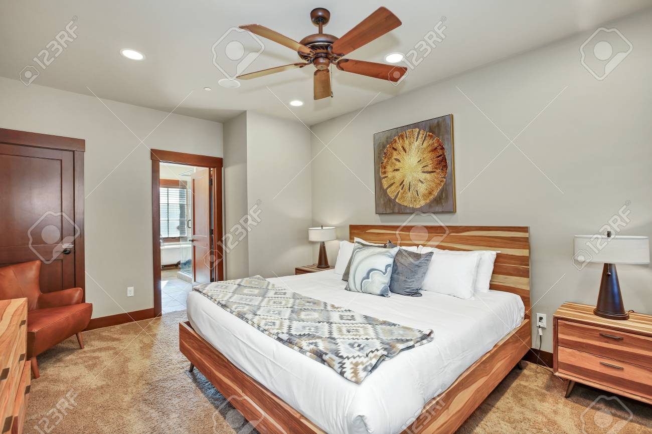 Cozy master bedroom interior features large wood bed with headboard...