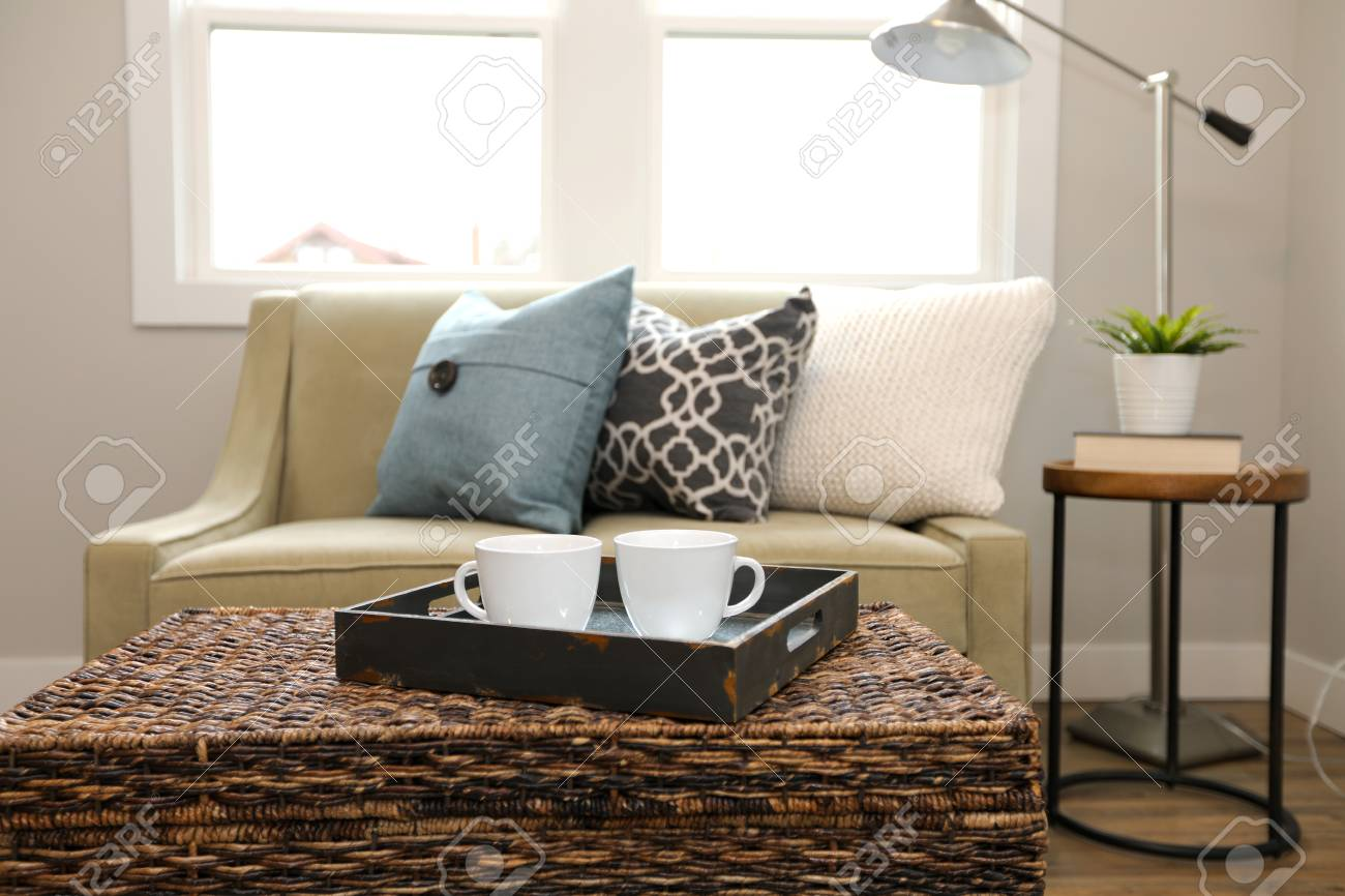 - Rattan Trunk Coffee Table With A Wood Tray And White Cups Next To