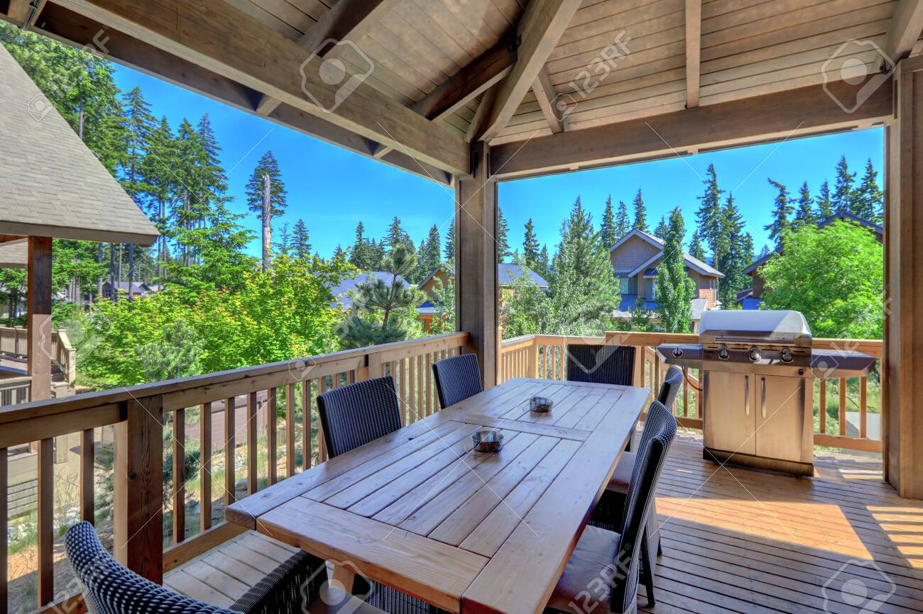 Beautiful covered deck with large luxury dining room table with grill and railings. Lots of pine trees. - 145078986