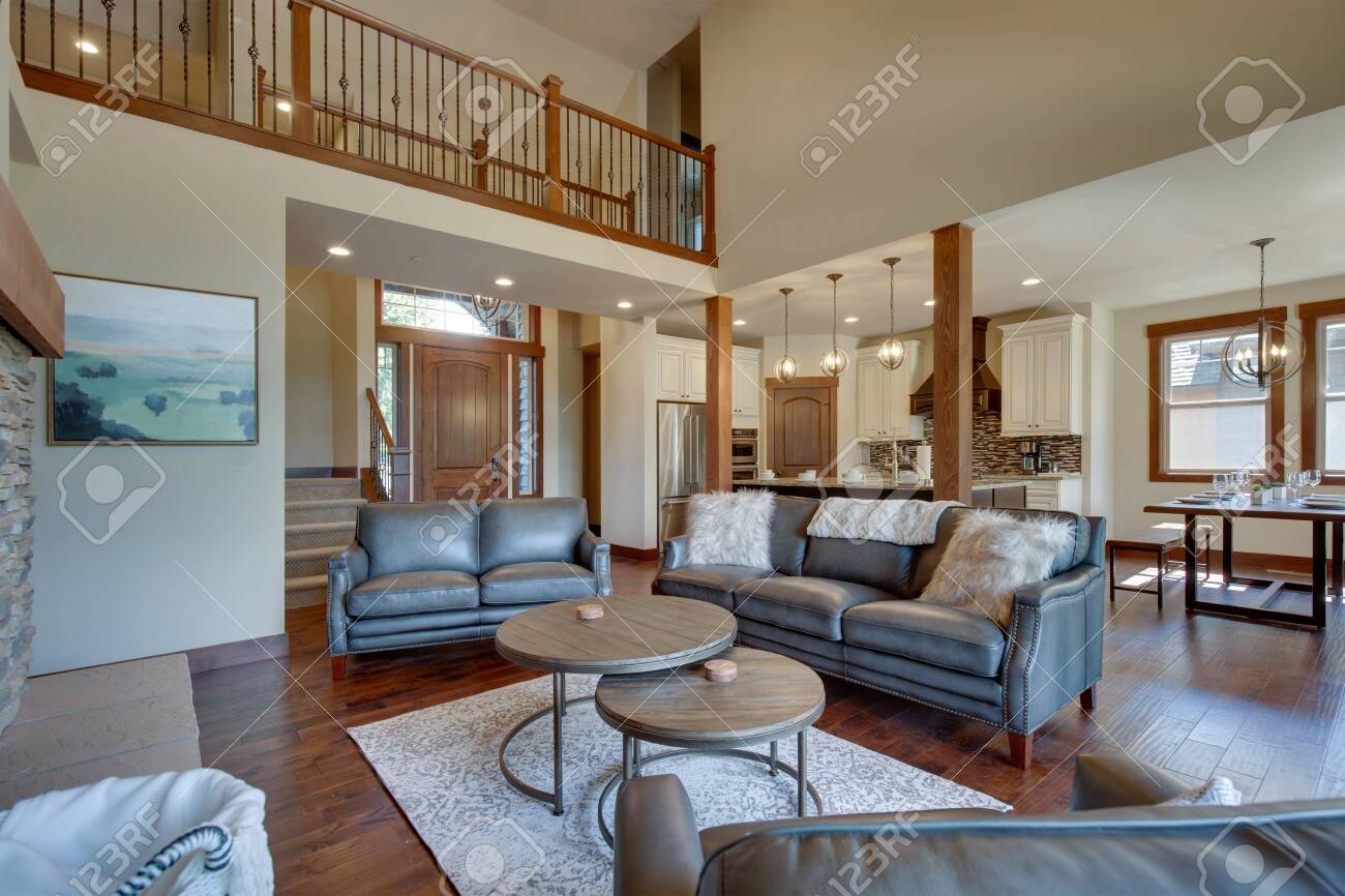 An absolute beautiful luxury living room with huge vaulted ceiling, fire place, harwood floor, amazing furniture, and lots of windows and doors. Solid wood rustic modern dining room table. - 142921889
