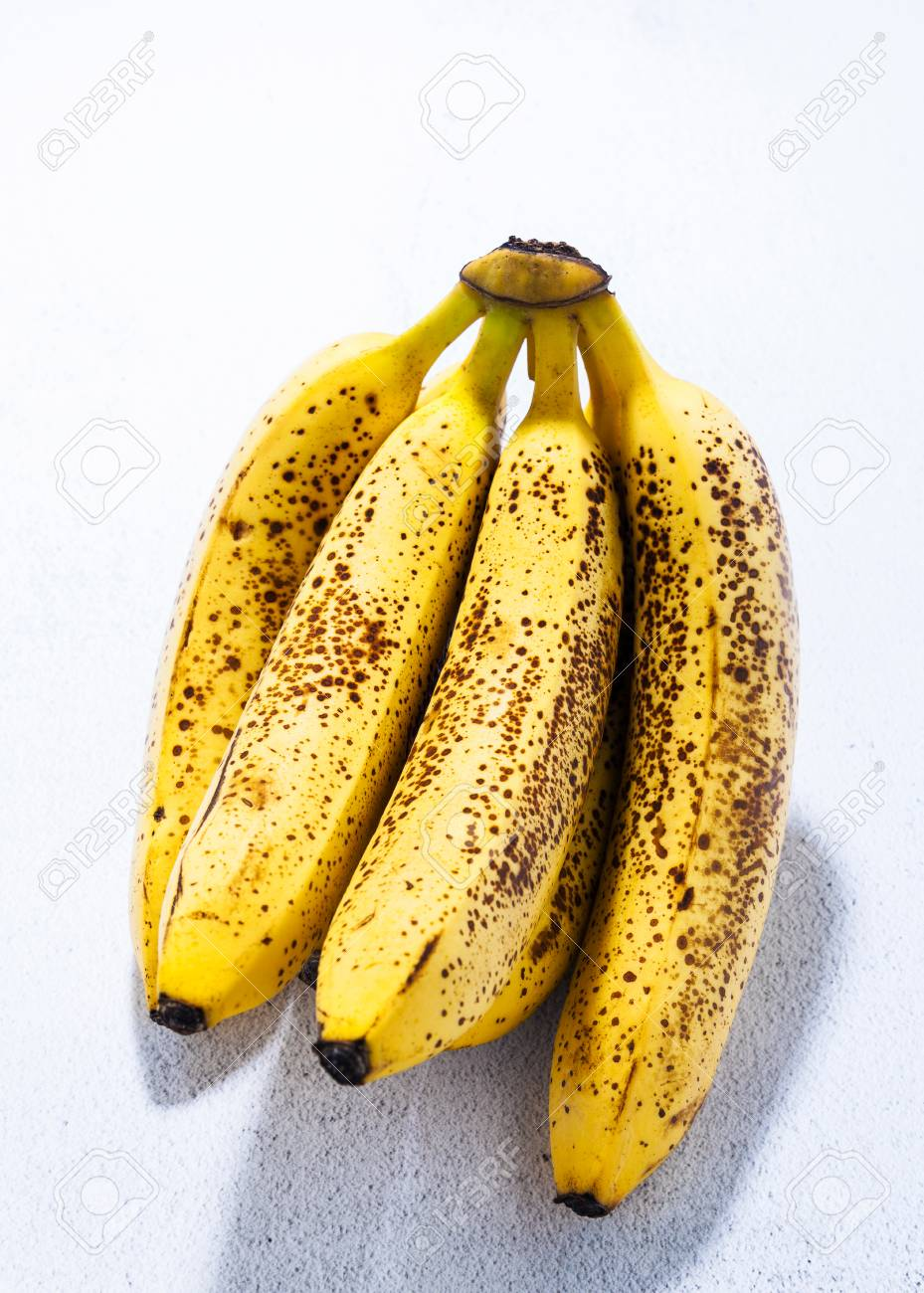 Banana On Table branch of overripe bananas with black dots on the table. natural sweetener.  concept of