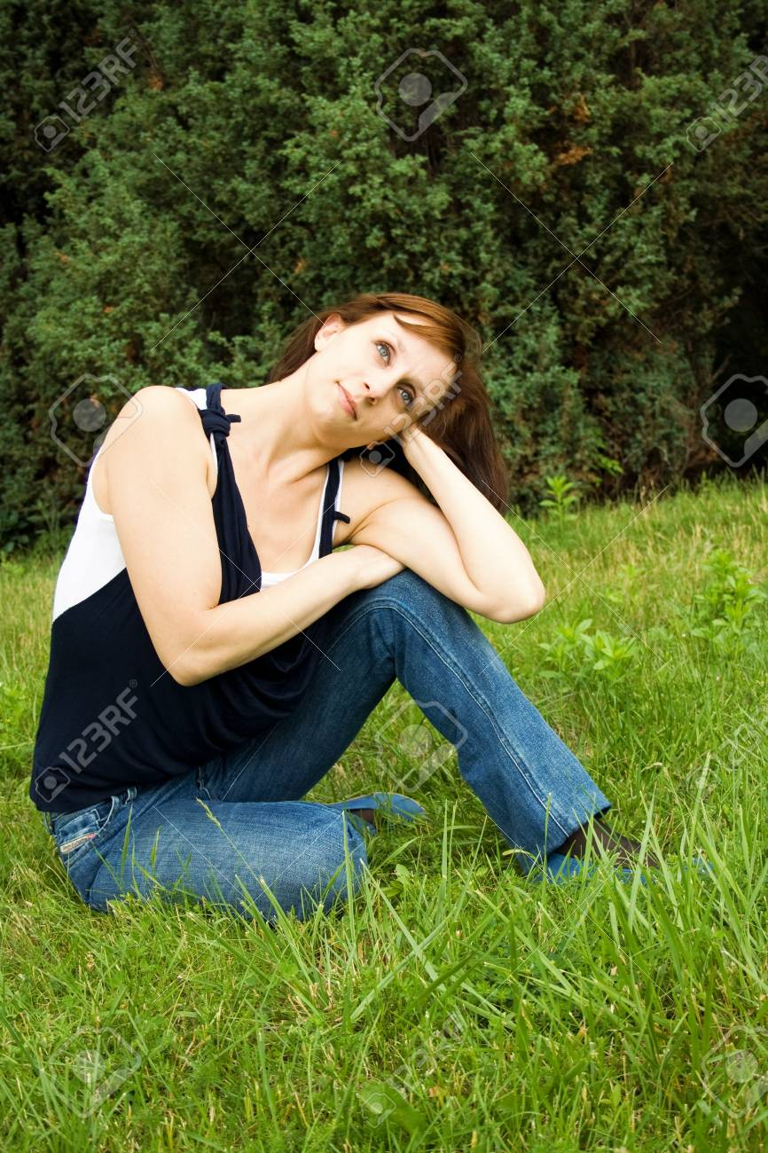 Young happy woman sitting on the green grass Stock Photo - 17423416