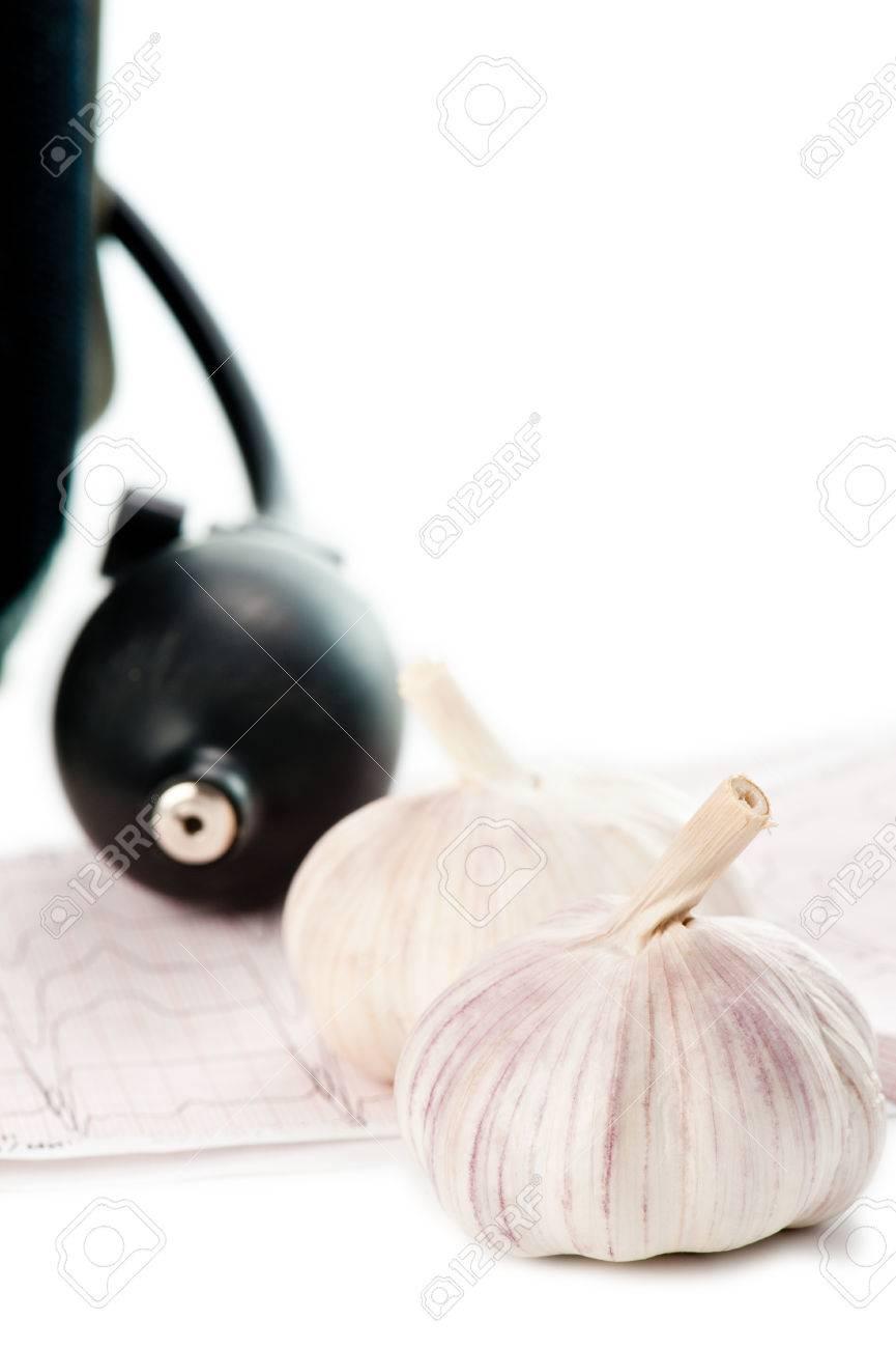26560286 sphygmomanometer and fresh garlic lying on ecg diagram sphygmomanometer and fresh garlic lying on ecg diagram stock photo