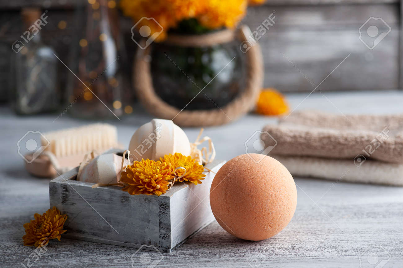 Aroma bath bombs in spa composition with orange flowers and towels. Aromatherapy arrangement, zen still life with lit candles - 158378048