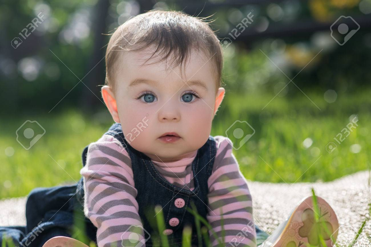 2e993ca2036c Cute Little Baby Girl With Big Blue Eyes And Long Eyelashes Sitting ...