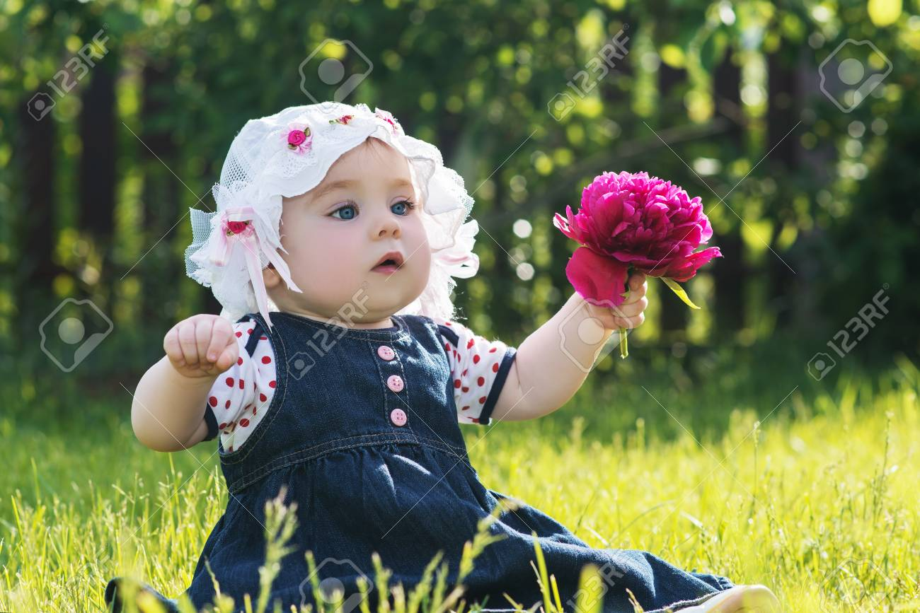 Cute baby girl in a summer hat sitting on a green grass on the nature and