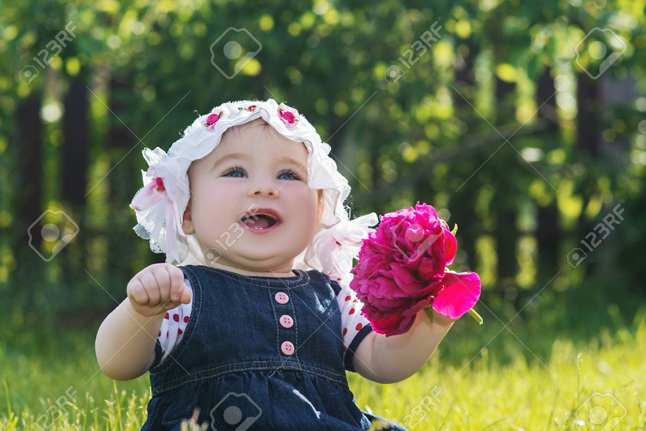 cute little baby girl sitting on the grass with flower in her