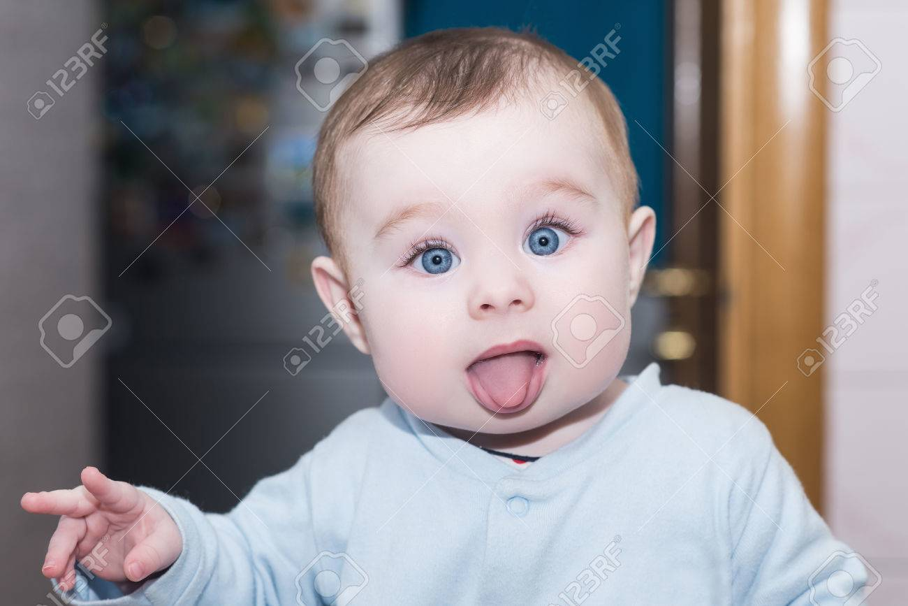 funny child shows tongue and points fingers. portrait of cute