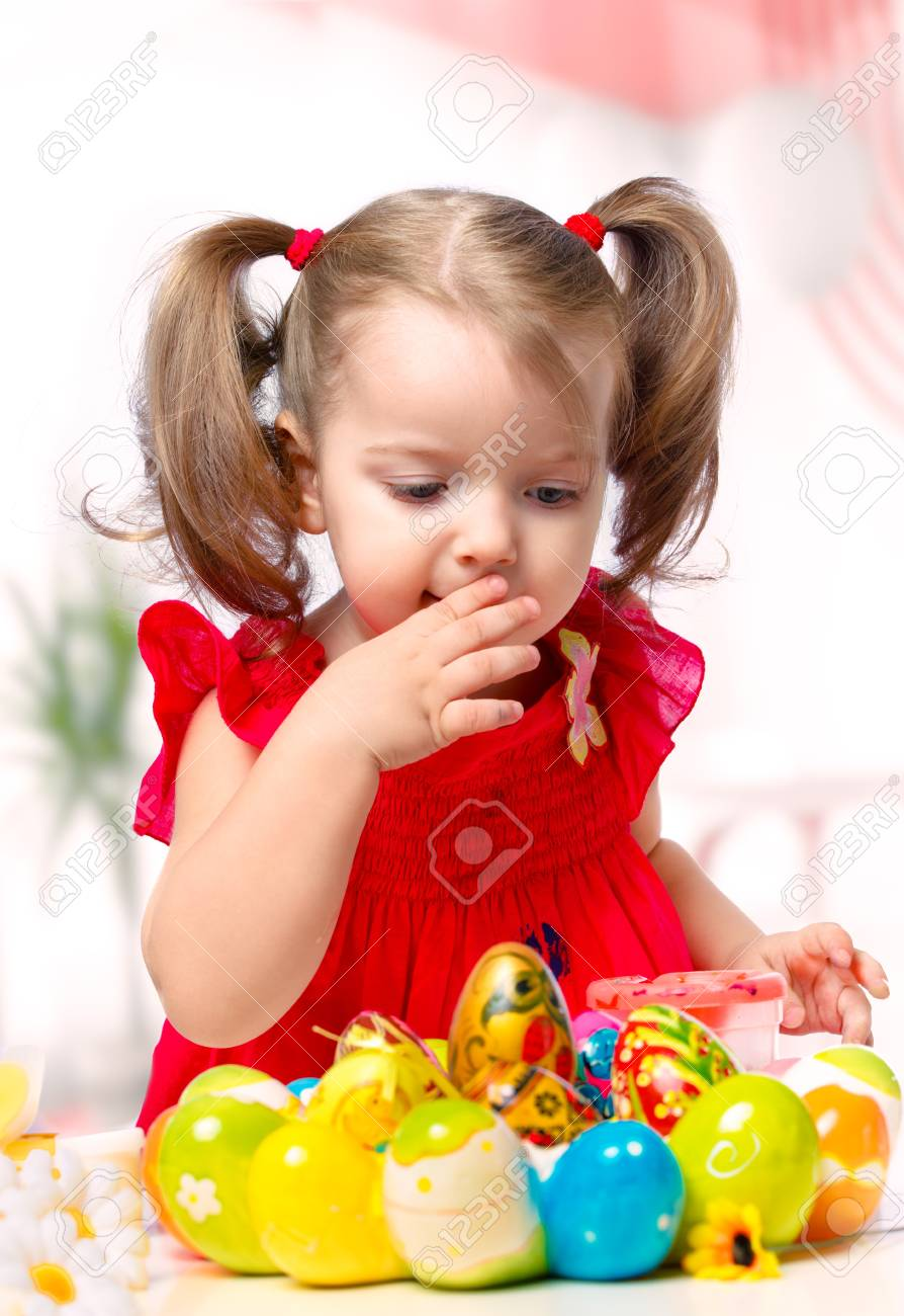 portrait of a little girl paints the eggs on a white background Stock Photo - 17079999