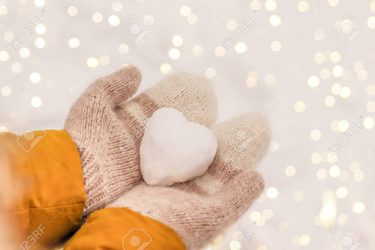 Hands in warm knit mittens with a snowy heart on a background of snow, Valentine's Day romantic concept - 113318739